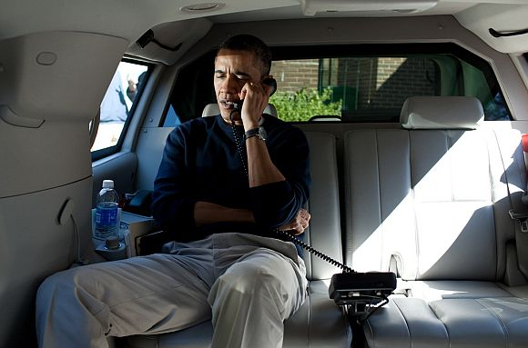 President Barack Obama talks on the phone with Afghanistan President Hamid Karzai from his vehicle to express his shock and sadness over the killing of Afghan civilians