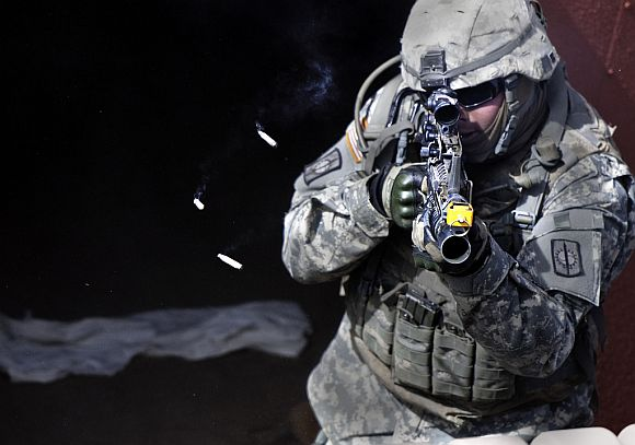 A US soldier fires at simulated enemy combatants during a field exercise