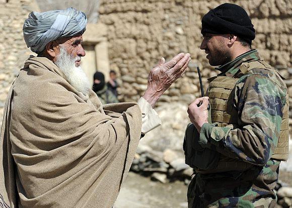 An Afghan National Army commando, right, conducts a key leader engagement with an Afghan village elder during a mission in search of insurgent weapons caches in Alahsang village, Wardak province, Afghanistan