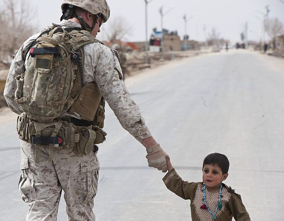 A US Marine hands with an Afghan child while on a walking tour of the bazaar in Marjeh, Afghanistan