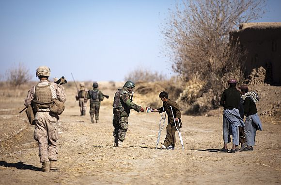 Afghan National Army soldier Taza Khan hands a bag of chips to a local boy, injured by an improvised explosive device, while patrolling with US Marines