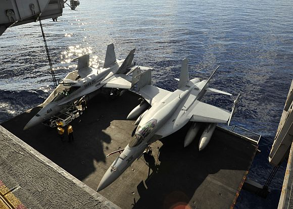 An F/A-18C Hornet assigned to the Thunderbolts of Marine Strike Fighter Squadron (VMFA) 251, left, and an F/A-18E Super Hornet assigned to the Knighthawks of Strike Fighter Squadron (VFA) 136 are lowered on an aircraft elevator to the hangar bay of the aircraft carrier USS Enterprise