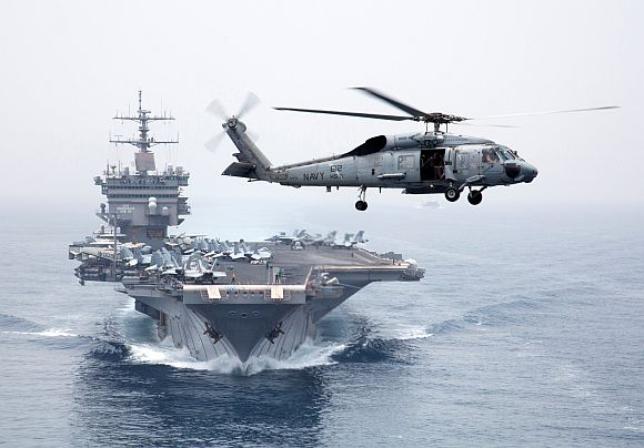 An HH-60H Sea Hawk helicopter, assigned to the Dragonslayers of Helicopter Anti-Submarine Squadron 11, flies in front of the aircraft carrier USS Enterprise as it transits the Strait of Bab el Mandeb