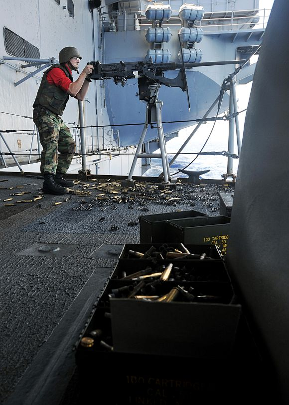 Petty Officer 3rd Class Christopher DiBernardo, gunner's mate, fires a .50-caliber machine gun during a quick draw exercise aboard the aircraft carrier USS Enterprise