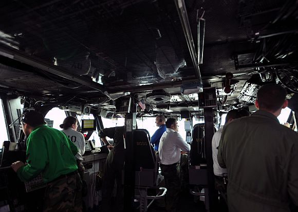 Sailors track the recovery of an aircraft in primary flight control during flight operations aboard the aircraft carrier USS Enterprise