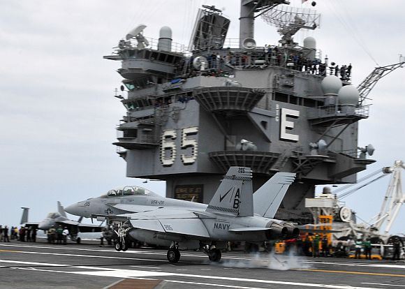 An F/A-18F Super Hornet assigned to the Checkmates of Strike Fighter Squadron 211 lands aboard the aircraft carrier USS Enterprise