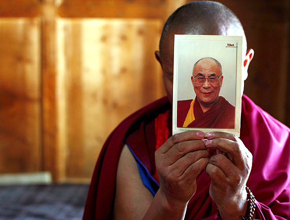 A monk holds a picture of Tibetan spiritual leader Dalai Lama