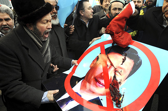 Ethnic Uighur demonstrators hold a defaced poster of China's Vice-President Xi Jinping