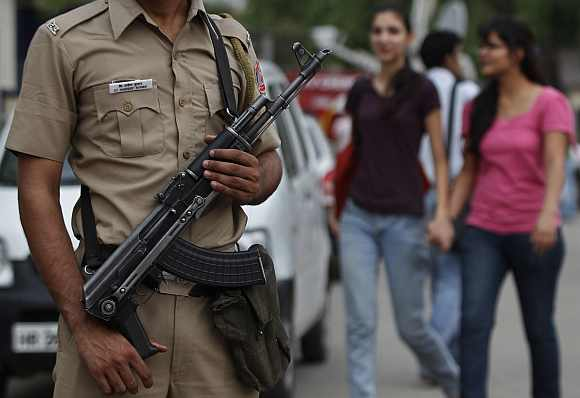 A policeman stands guard as girls walk past outside a market in New Delhi
