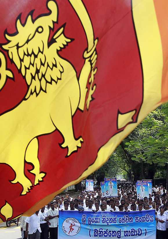Demonstrators hold up images of the Sri Lanka's president Mahinda Rajapaksa in front of the United Nations head office during a protest in Colombo March 15