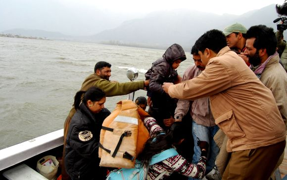 Tourists being rescued from the houseboats at Dal Lake during the windstorm in Srinagar, on Tuesday