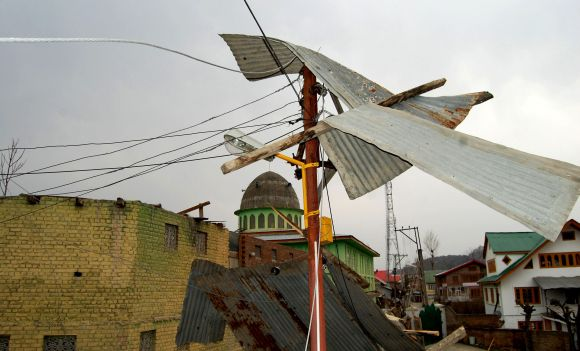 The roof of a damaged house is seen entangled in electrical wires at a transformer in Srinagar