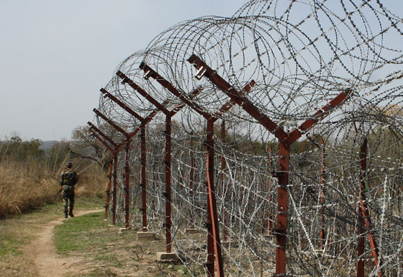 A soldier walks past the electric fencing inside the Line of Control in Jammu & Kashmir.