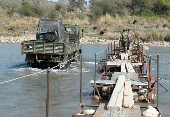 A river without a road bridge, where a big vehicle carries smaller vehicles across.