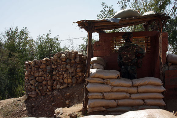A soldier stands his guard, observing the LoC. At some posts, the Pakistani post is less than 70 metres away