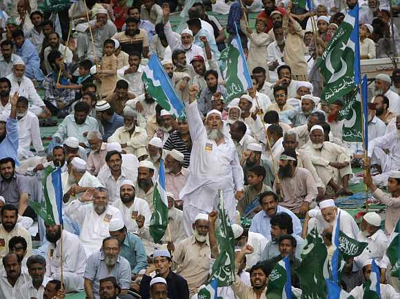 A supporter of the religious and political party, Jamaat-e-Islami, shouts slogans as hundreds gather to protest against drone attacks, in Karachi