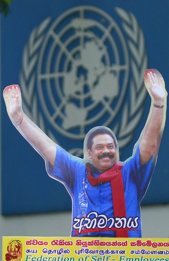 A demonstrator holds up an image of Sri Lanka's president Mahinda Rajapaksa in front of the United Nations head office during a protest in Colombo