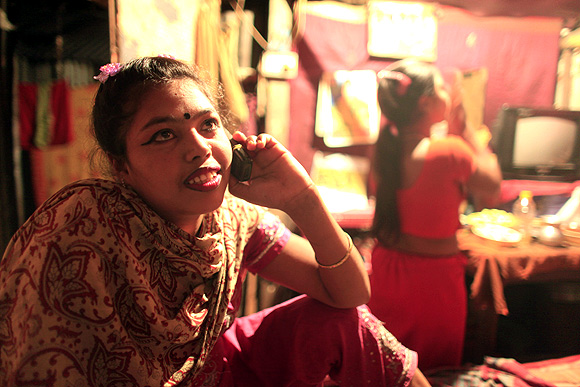 Sixteen-year-old Maya, a prostitute, talks on the phone inside her small room at Kandapara brothel in Tangail