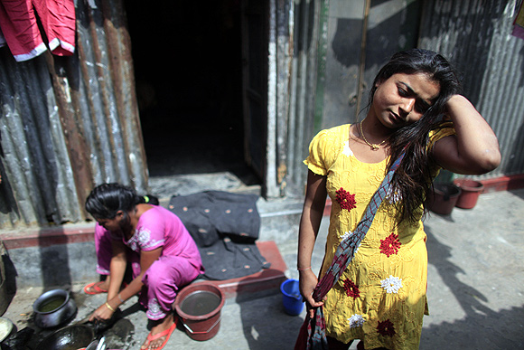 Seventeen-year-old prostitute Hashi stands in front of her small room at Kandapara brothel in Tangail, a northeastern city of Bangladesh