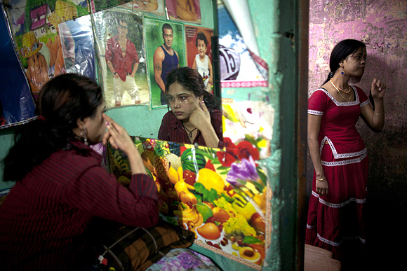 Prostitutes apply makeup as they try to attract customers inside a brothel in Faridpur