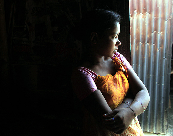 Fourteen-year-old prostitute Lipi waits for customers at a brothel in Faridpur