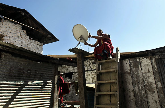 A Buddhist monk fixes a television satellite dish at a monastery in Tawang in Arunachal Pradesh