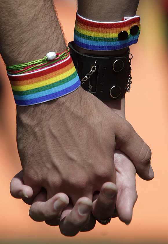Two men hold hands as they attend a march against homophobia