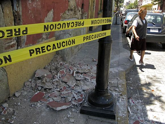 A resident evades rubble after an earthquake, in Oaxaca