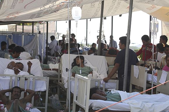 Patients evacuated from a hospital damaged by an earthquake on Tuesday lie in a makeshift emergency room in Ometepec in the Mexican state of Guerrero