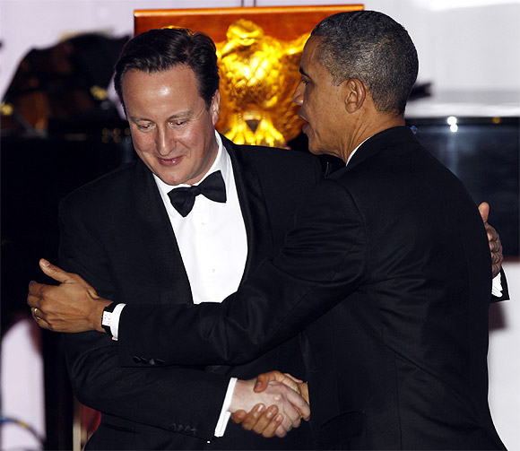 US President Barack Obama and British Prime Minister David Cameron embrace after a toast during the State Dinner at the White House in Washington