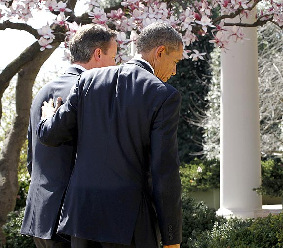 Obama and Cameron leave after their press conference in the Rose Garden of the White House in Washington