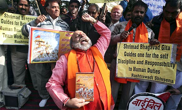 Activists shout slogans during a protest against the plea to ban Gita
