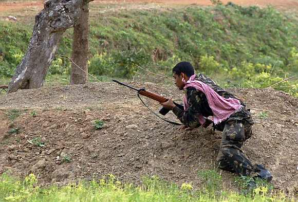 A paramilitary soldier takes up position during a gunfight with Maoist rebels in Pirrakuli village near Lalgarh, in the West Midnapore district, some 170 km of Kolkata