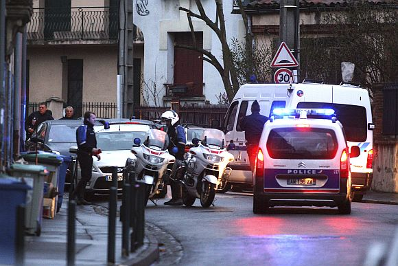 Masked French special intervention police (RAID) member arrives on the scene during a raid on a house to arrest the gunman