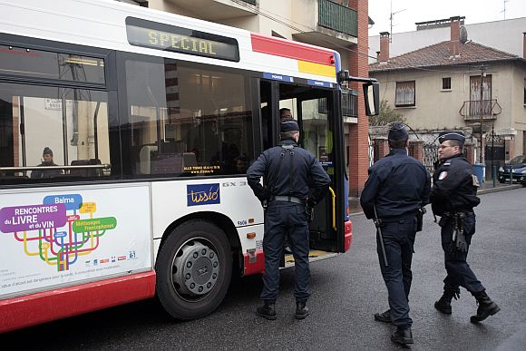 Police enter a city bus which arrives in the neighbourhood to evacuate residents who live in the house where police conduct a raid to arrest suspects in the killings of three children and a rabbi on Monday at a Jewish school, in Toulouse