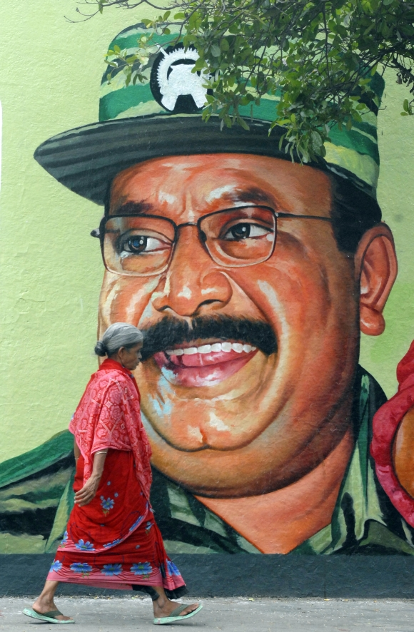 A woman walks past a portrait of late LTTE leader Prabhakaran