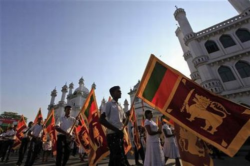 Sri Lankans hold national flags as they march against the UN resolution calling on Sri Lanka to probe wartime human rights abuses, in Colombo.
