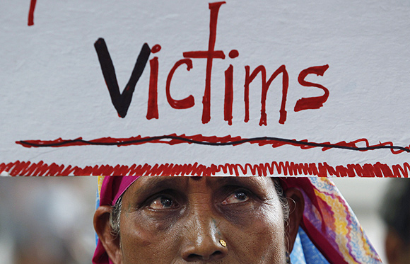 A victim of the 1984 Bhopal gas tragedy holds a placard during a demonstration