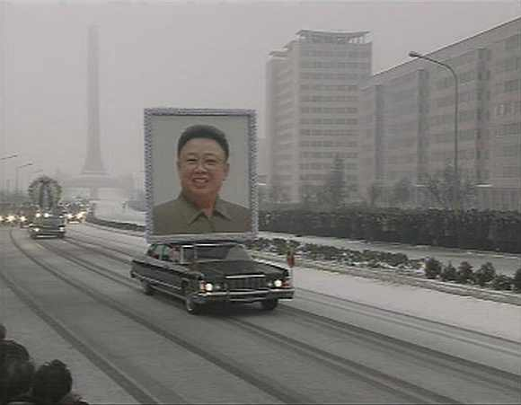 A limousine carrying a portrait of late North Korean leader Kim Jong-il leads his funeral procession past crowds in Pyongyang on December 28, 2011