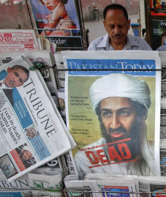 A roadside vendor sells newspapers with headlines about the death of Al Qaeda leader Osama bin Laden in Lahore