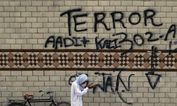 A man prays, next to graffiti painted road-side, during an anti-Taliban rally in Rawalpindi
