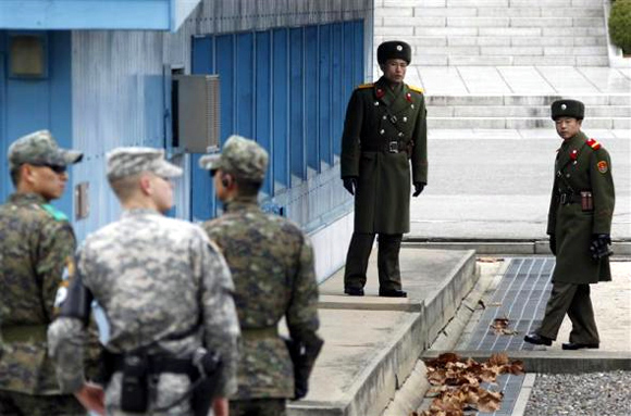 North Korean soldiers look across a concrete border as a US Army soldier and South Korean soldiers stand guard at the DMZ