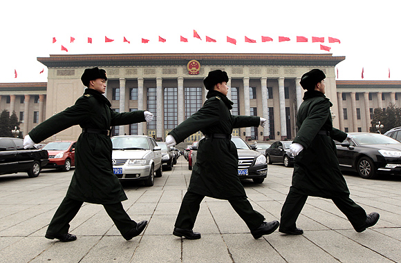 Soldiers of the Chinese People's Liberation Army march in front of the Great Hall of the People