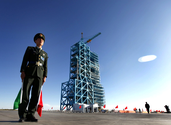 A Chinese soldier stands beside a Long March II-F rocket
