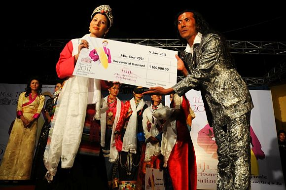 Miss Tibet pageant director Lobsang Wangyal presenting the winners cheque to Tenzin Yangkyi