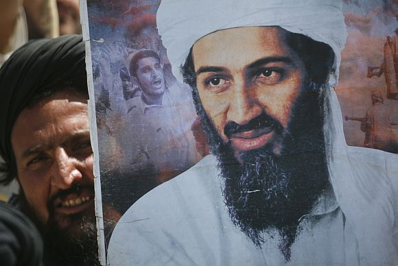 A supporter of the Pakistani religious party Jamiat-e-ulema-e-Islam holds an image of Al Qaeda leader Osama bin Laden during an anti-US rally on the outskirts of Quetta, on May 6, 2011.
