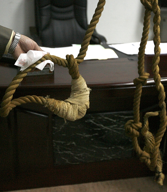 A museum worker shows to reporters a noose that will be displayed in a new Iraqi museum in Baghdad