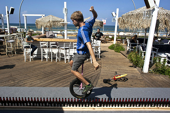 Riding unicycle on beer bottles