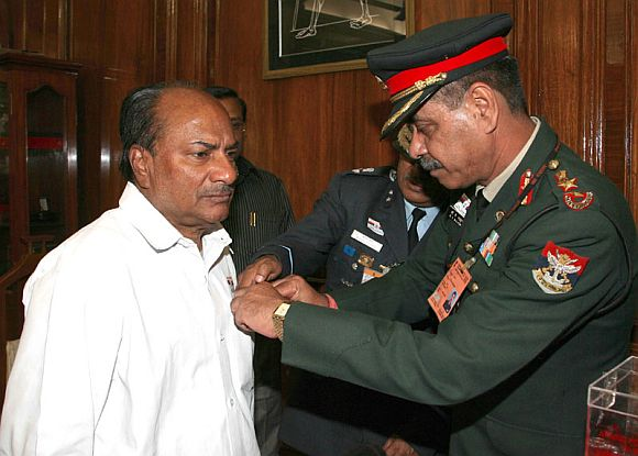 File photo shows Col B K Majumdar of the Kendriya Sainik Board pinning a lapel on the Defence Minister A K Antony, on the occasion of the Armed Forces Flag Day, in New Delhi on December 07, 2011