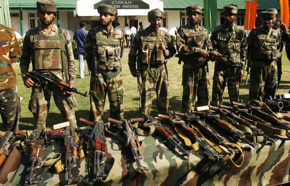 Army soldiers stand behind a display of seized arms and ammunition in Srinagar